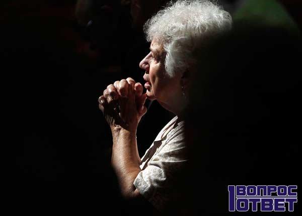 Женщина молится за упокой мужа и родственников