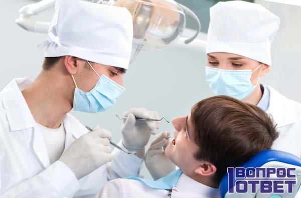 Стоматологи осматривают зубы и десна