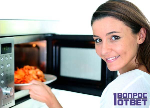 Девушка ставит пищу в рабочую микроволновую печь