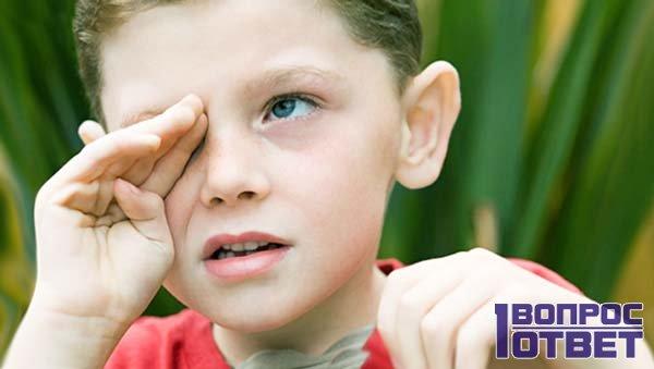 Мальчик трет правый глаз