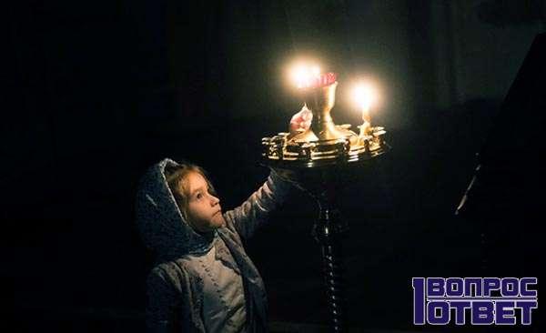 Ставит свечи в церкви