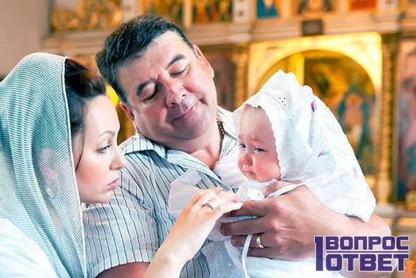 Крестный держит девочку на руках