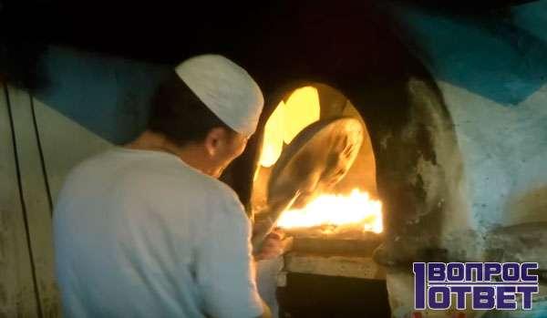 Узбек готовит мясо в стационарной печи